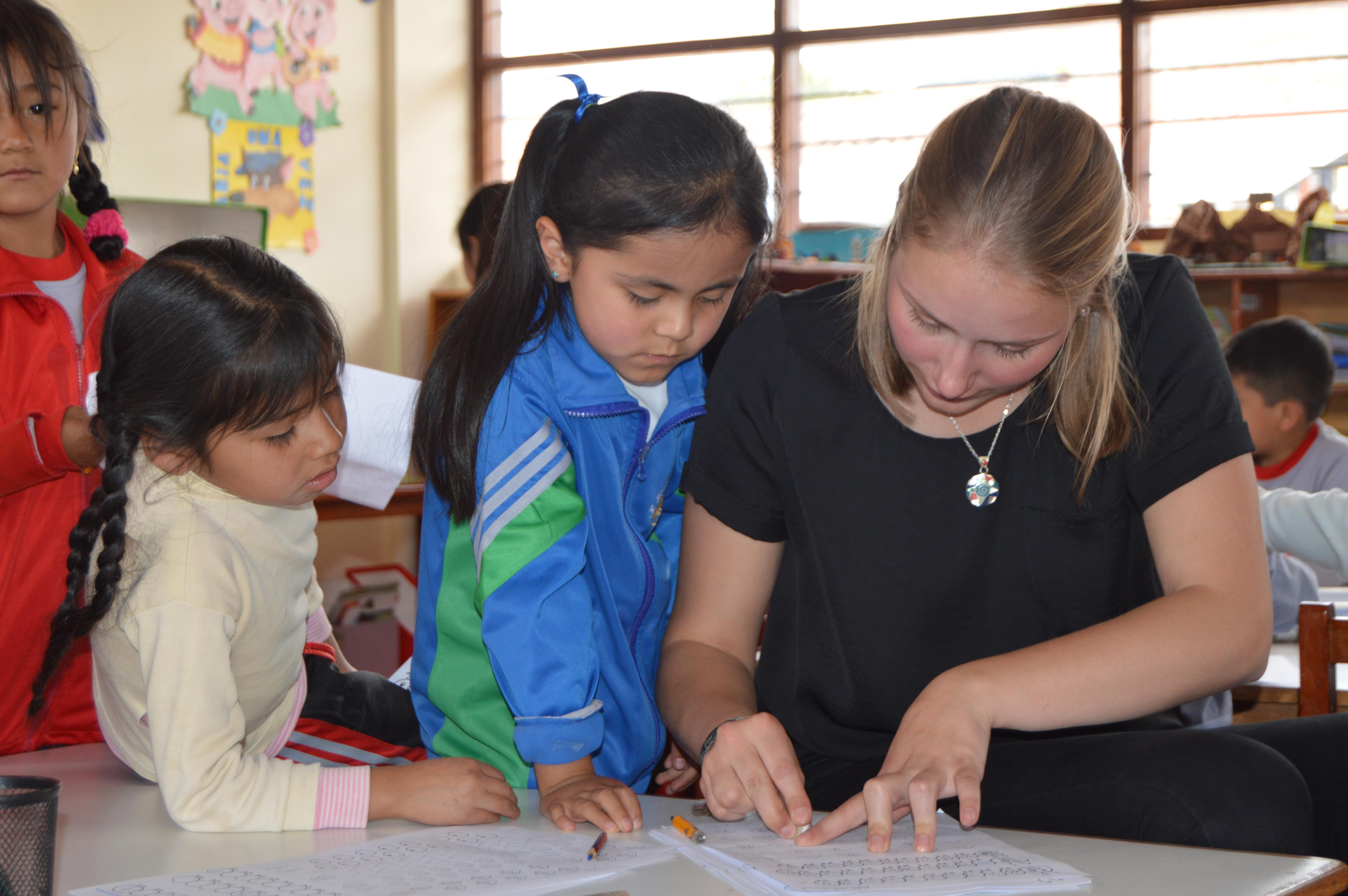 Teaching volunteer in Peru explains to her student where she went wrong in her work and how to correct it